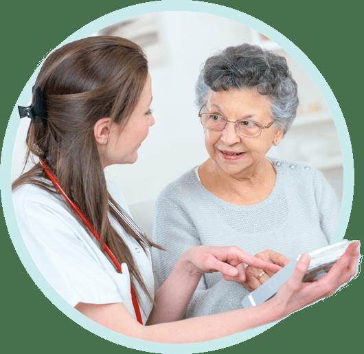 verzorger met oudere dame legt tablet uit